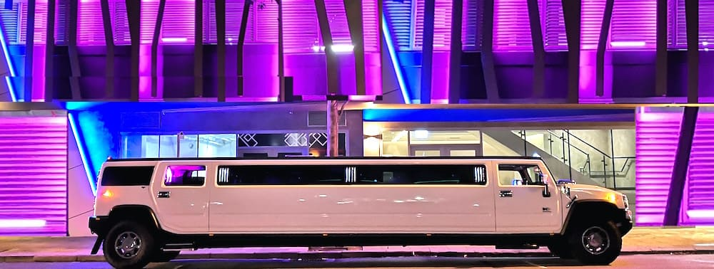 Best Hummer Limo Perth 16 Seater White Limousine at night near the pink lights of St Georges Terrace