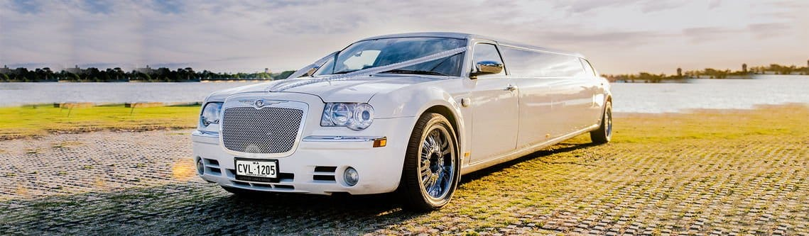 Lush Limos luxury White Chrysler Limousine at the boat ramp by the river during a photo for the wedding limousine hire.